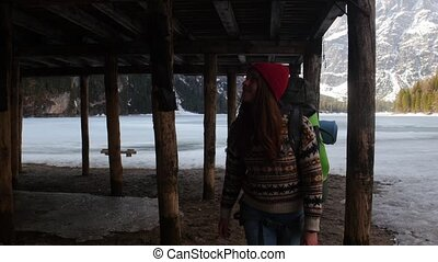 Young pretty woman walking on a lago di braies coast with a...