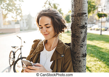 Young pretty woman walking outdoors in park in beautiful spring day using mobile phone.