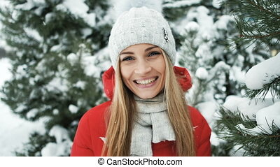 Young pretty woman warm in ray of sun in winter forest.