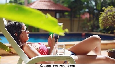 Young pretty woman wearing sunglasses and bikini using tablet lying on sunbed by pool. 1920x1080