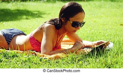Young pretty woman wearing sunglasses and bikini with tablet computer on meadow in the grass. 3840x2160