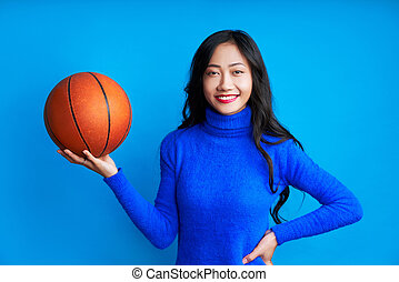 Young pretty woman with basketball in hand isolated on blue background