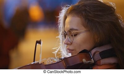 Young pretty woman with curly hair playing violin in subway,...