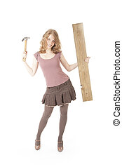 young pretty woman with hammer and wood against white...