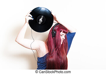 Young pretty woman with headphones and vinyl disk