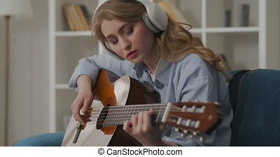 young pretty woman with headphones on head is studying to play guitar, alone in apartment at weekend
