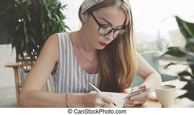 Young pretty woman writing information from card to notebook . Female writing in cafe.