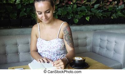 Young prety woman with tattoo writing in her journal, diary.