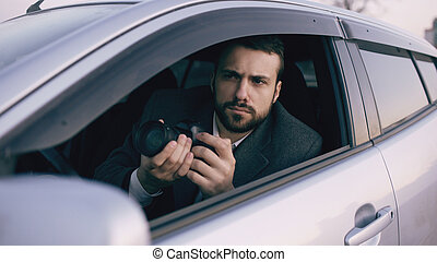 Young private detective man sitting inside car and photographing with dslr camera
