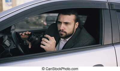 Young private detective man sitting inside car and...