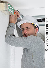 young professional electrician at work in building