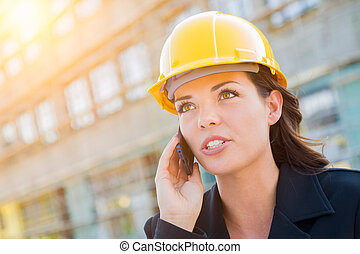 Young Professional Female Contractor Wearing Hard Hat at Contruction Site Using Cell Phone.