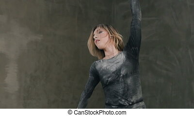 Young professional female dancer is performing acrobatic dance in acloud white smoke dust or white powder. Dance girl dancing the modern dance in black body suit and shorts on the scene