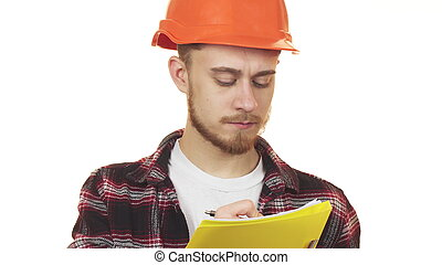 Young professional male architect in a hardhat making notes