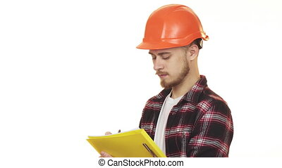 Young professional male contractor in hardhat making notes smiling
