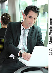 Young professional riding the tram typing on laptop computer