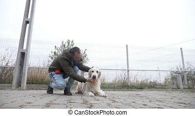 Young professional trainer rewarding his dog for listening...