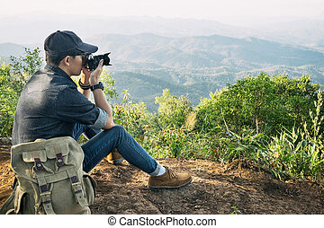 Young professional travrler man with camera shooting...