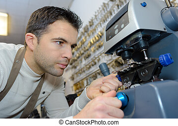 young professional with different types of keys in locksmith