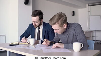 Young professionals work on blueprint at table in modern office.