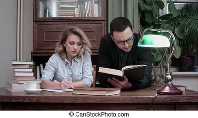 Young professor in glasses helping female student with her report