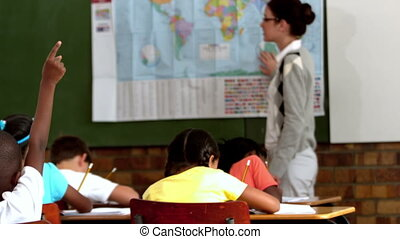 Young pupil raising hand during geography lesson in...