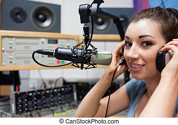Young radio host putting her headphones on