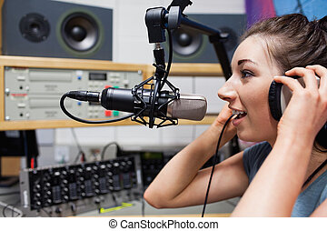 Young radio host speaking through a microphone