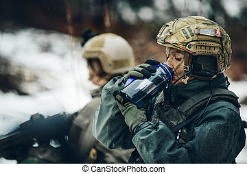 young ranger member drink water in forest