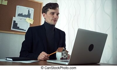 Young real estate agent having video call with customer...