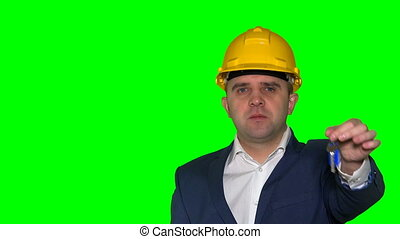 young realtor business man with helmet hold new house construction keys