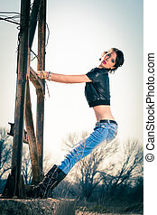 young rebel woman in blue jeans, leather boots and leather jacket outdoor shot on old metal construction, full body shot