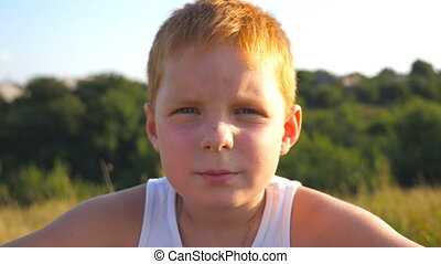 Young red hair boy with freckles looking at camera with serious expression at face outdoors. Portrait of sad children with emotions and feelings. Close up Slow motion