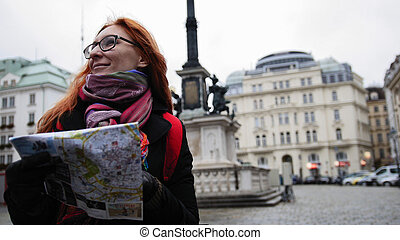 Young red hair woman using city map in Vienna, wide angle