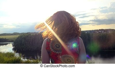 Young red-haired curly haired woman enjoys  landscape standing on a mountain looks at sun  in feeling happiness and freedom
