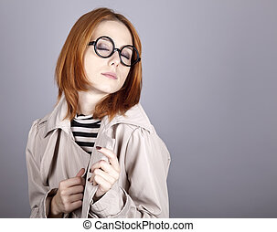 Young red-haired girl in glasses and cloak.