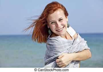 Young red-haired girl on the beach