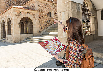 Young red-haired tourist with a backpack consults a map in the main square of Caceres, next to the old town