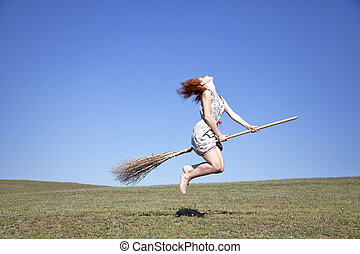 Young red-haired witch on broom flying over green grass ...