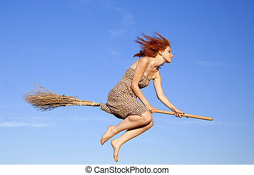 Young red-haired witch on broom flying away