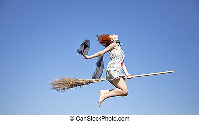 Young red-haired witch on broom flying in the sky