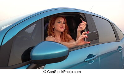 Young red-haired woman doing selfie smartphone in her car