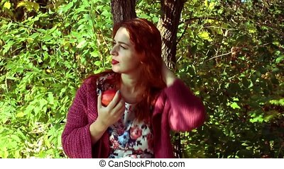 young red-haired woman in the autumn park