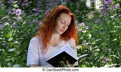 Young red-haired woman reads a book among flowers in a city ...