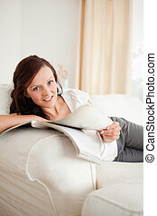 Young red-haired woman studying on the sofa looking into the camera in the livingroom