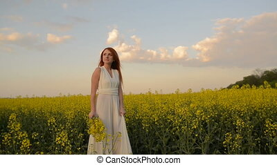 Young red-haired woman walking in the middle of a blooming field and smiling, slow motion