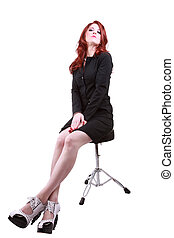 Young red headed woman on stool business dress