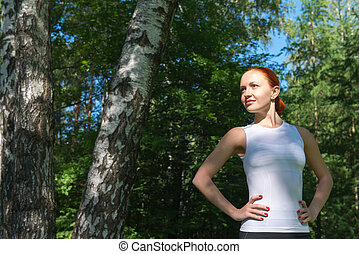 Young red woman standing in forest