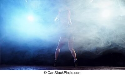 Young redhaired sexy strip dancer dancing in a smoke