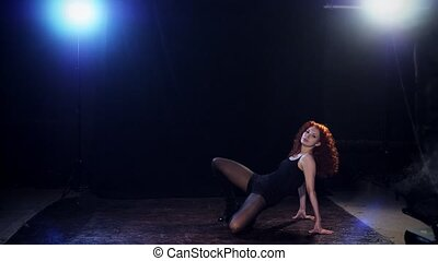 Young redhaired sexy strip dancer dancing on black background